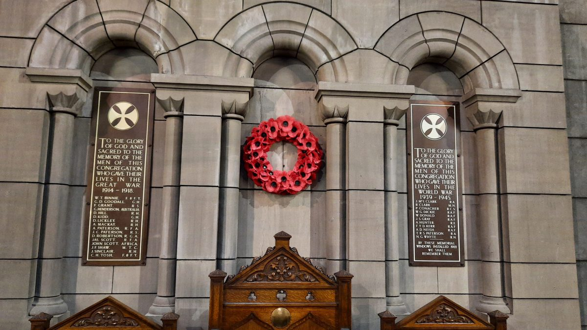 Image of wall behind communion table featuring poppy wreath