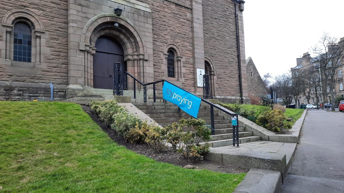 Front of our church with the Try Praying banner and booklets