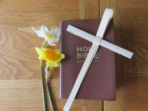 A bible with a palm cross on it, with two daffodials